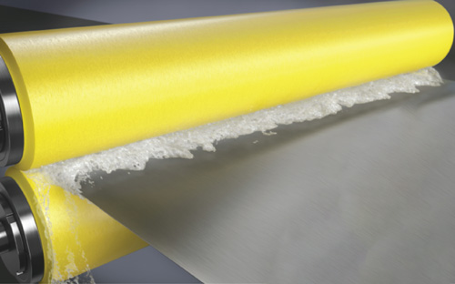A pair of NCCM<sup>®</sup> Premier Yellow nonwoven rolls wringing fluid from a metal strip.